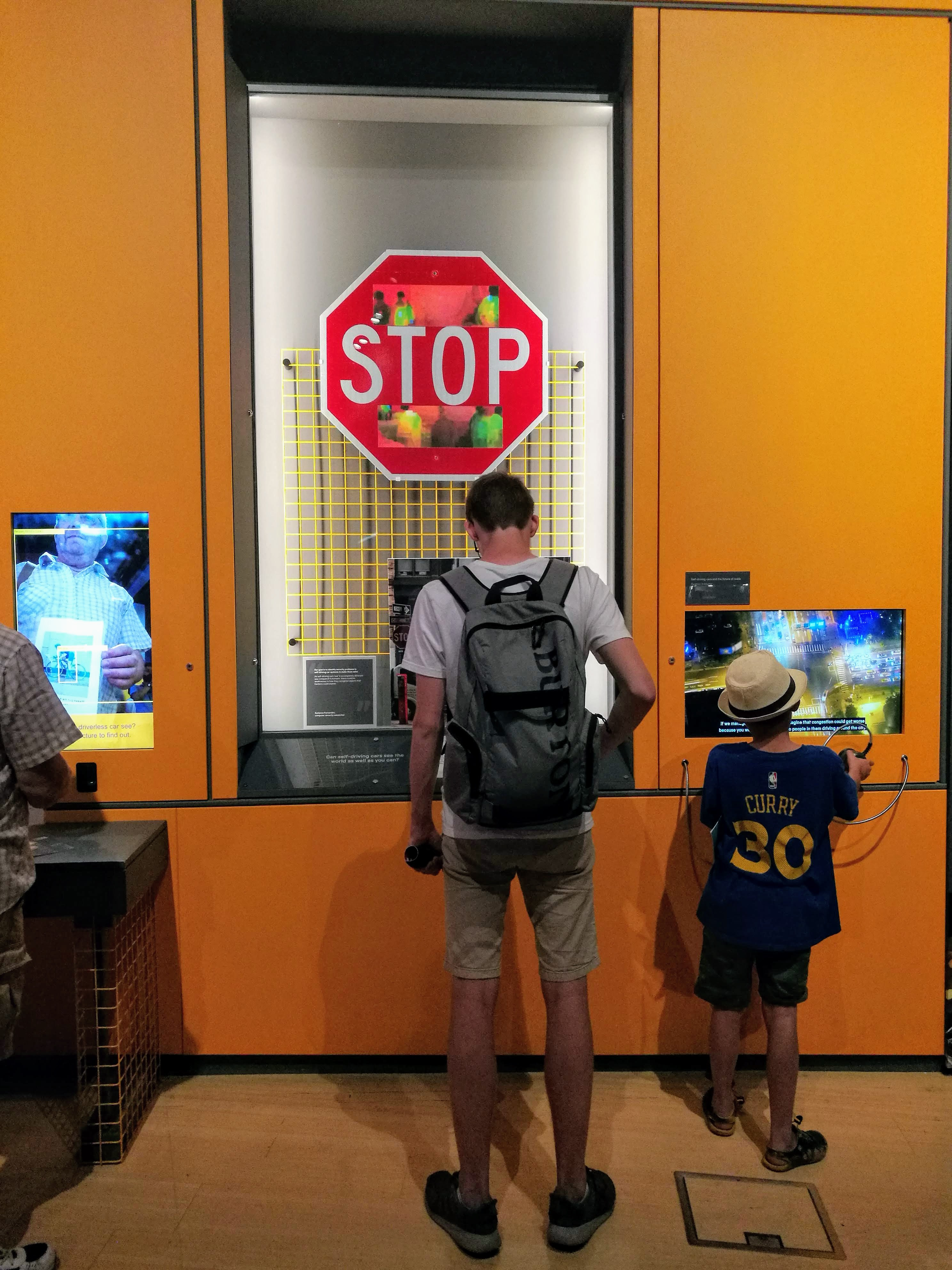 Visitors examine a display that shows a stop sign with stickers at the top and bottom of the sign.